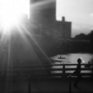 The sun sets over a pond with boaters in the heart of Akasaka